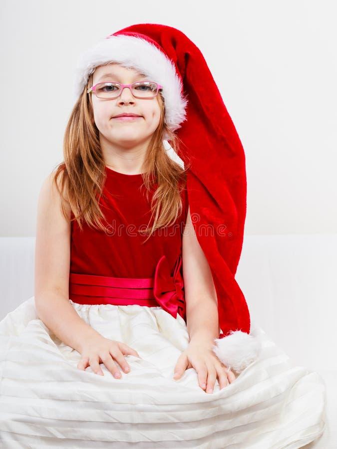 Ragazza di Natale in attrezzatura festiva del cappello di Santa immagine stock libera da diritti