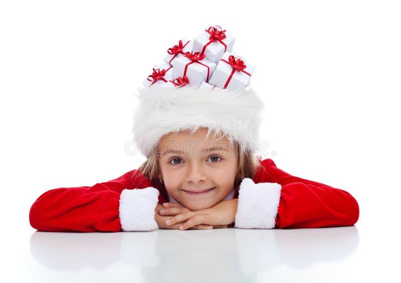 Ragazza di Natale con i lotti dei presente in suo cappello di Santa immagine stock libera da diritti