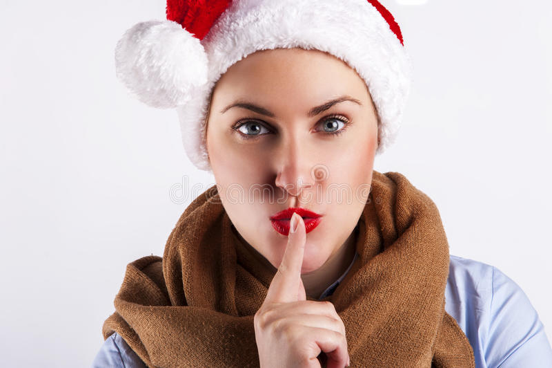 Ragazza di Natale felice in Santa Hat che fa un segno di silenzio immagine stock