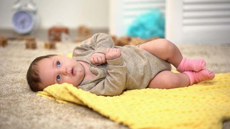 Ragazza di neonato adorabile sulla coperta, sviluppo muscolare, attivit? di giorno fotografia stock libera da diritti