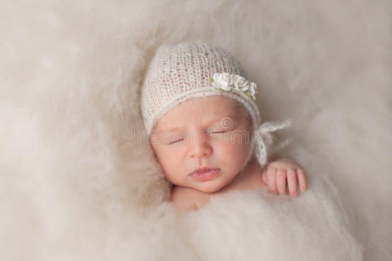 Ragazza di neonato che indossa un cofano tricottato bianco fotografia stock