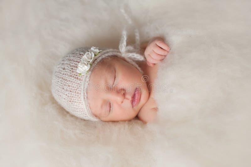 Ragazza di neonato che indossa un cofano tricottato bianco immagini stock