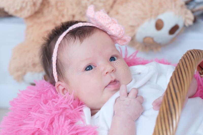 Ragazza di neonato in merce nel carrello di menzogne generale rosa, ritratto sveglio fotografia stock