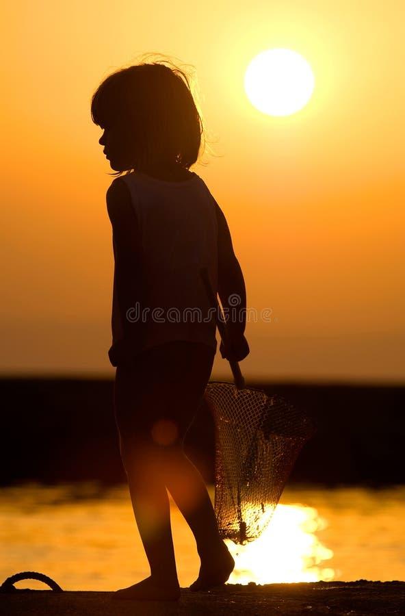 Ragazza di pesca nel tramonto fotografia stock