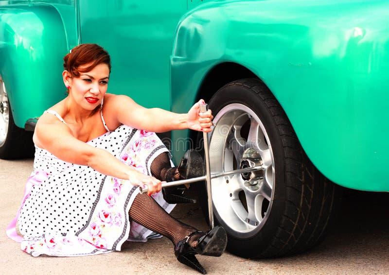 Ragazza di Pinup che cambia una gomma del camion fotografie stock libere da diritti