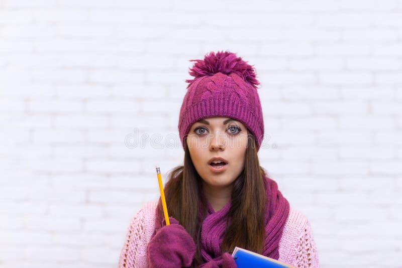 Ragazza di Pondering Worried Attractive dello studente in matita rosa della cartella della tenuta del cappello immagine stock