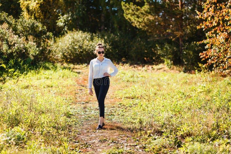 Ragazza di quindici anni alla moda in una camicia bianca e nei pantaloni neri nel legno fotografia stock libera da diritti