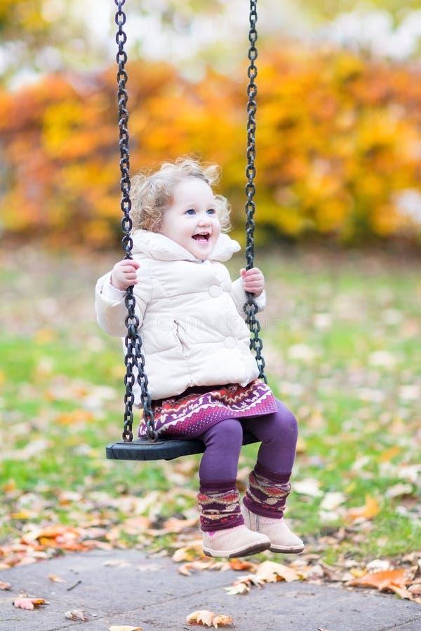 Ragazza di risata felice del bambino che gioca sull'oscillazione fotografia stock libera da diritti