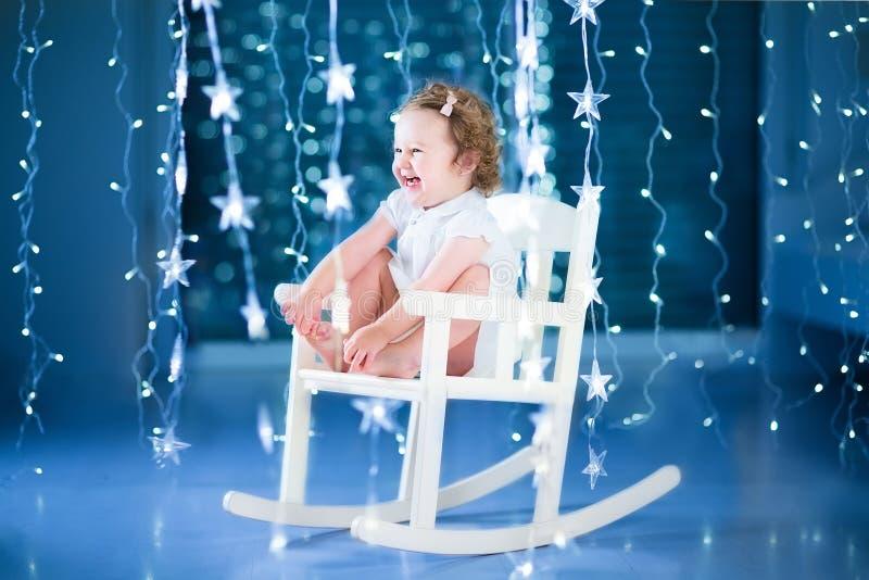 Ragazza di risata felice del bambino che gioca in una sedia di oscillazione bianca dentro immagine stock