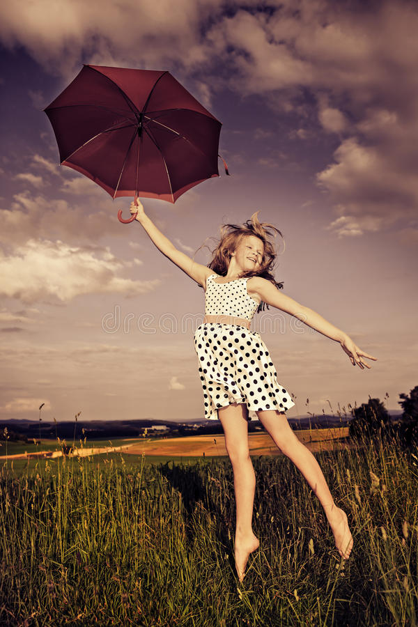 Ragazza di salto con l'ombrello immagine stock