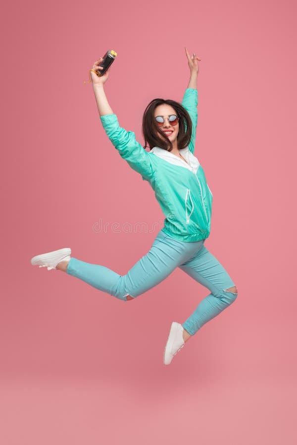 Ragazza di salto dei pantaloni a vita bassa con la macchina fotografica a disposizione fotografia stock libera da diritti