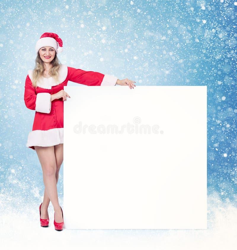 Ragazza di Santa che tiene grande insegna vuota quadrata bianca, su fondo e su neve blu immagini stock