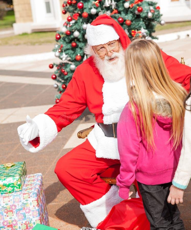 Ragazza di Santa Claus Gesturing While Looking At immagine stock