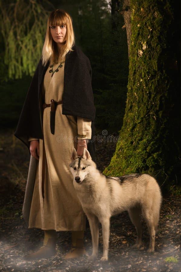 Ragazza di Slavonian e husky siberiano nella foresta profonda immagini stock libere da diritti