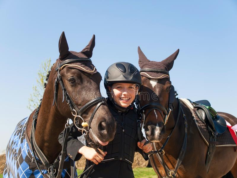 Ragazza di Smilling felice dopo la vittoria la concorrenza di showjumping con i suoi due cavalli fotografia stock libera da diritti