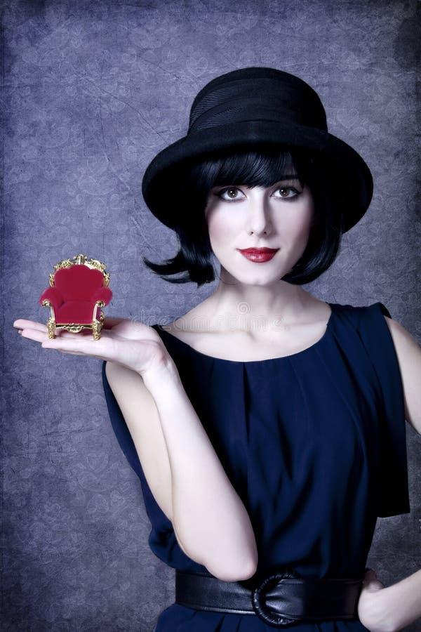Ragazza di stile in poltrona del giocattolo della tenuta del cappello. fotografia stock
