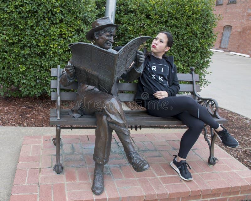 Ragazza di tredici anni che posa umoristico con il bronzo di Will Rogers su un banco, Claremore, Oklahoma fotografia stock