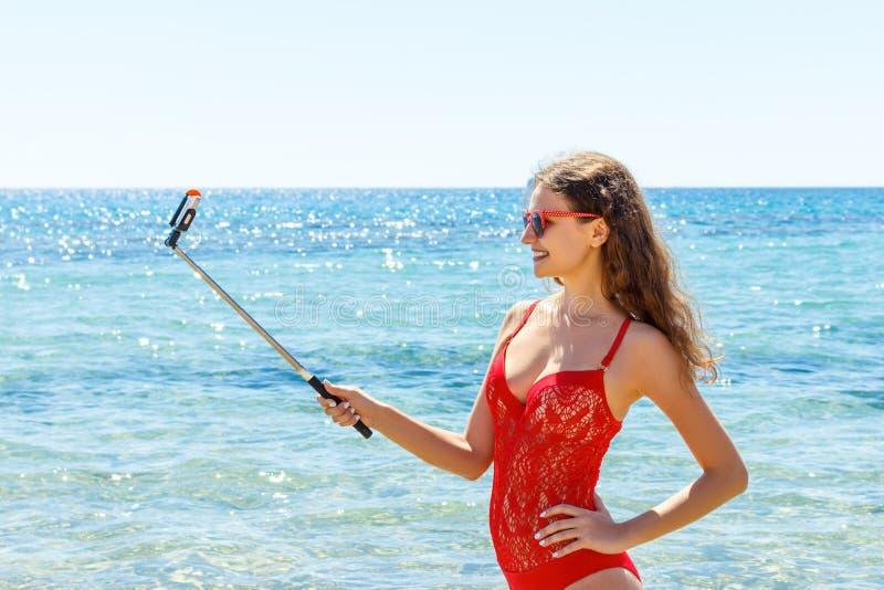 Ragazza di vacanza della spiaggia di estate che prende a divertimento la foto mobile del selfie con lo smartphone Ragazza che ind fotografia stock libera da diritti