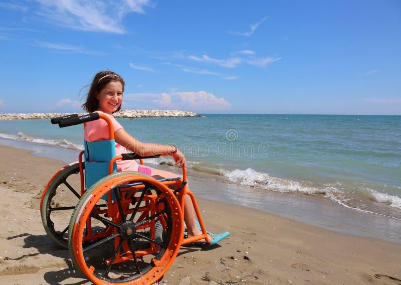 Ragazza disabile che si siede in una sedia a rotelle davanti al mare immagini stock