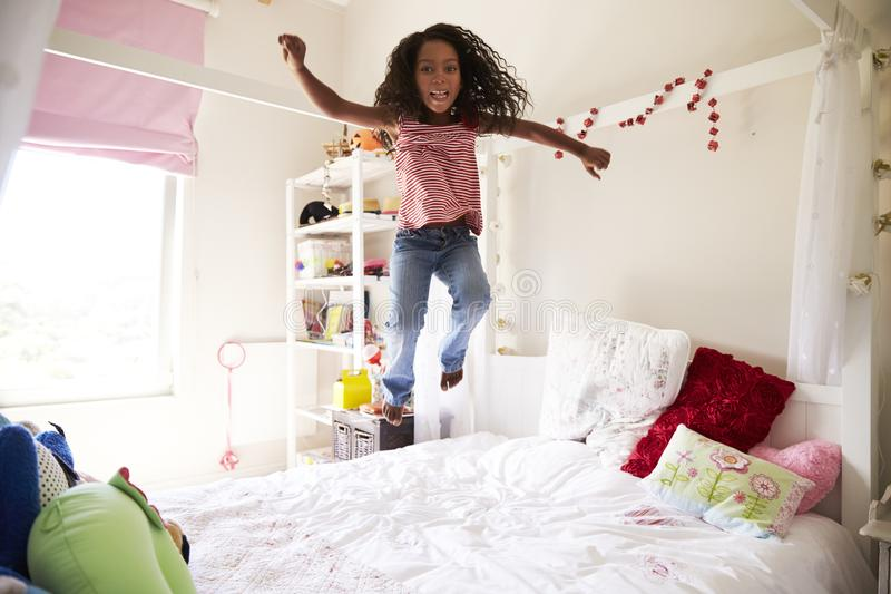 Ragazza divertendosi salto sul letto in camera da letto immagine stock