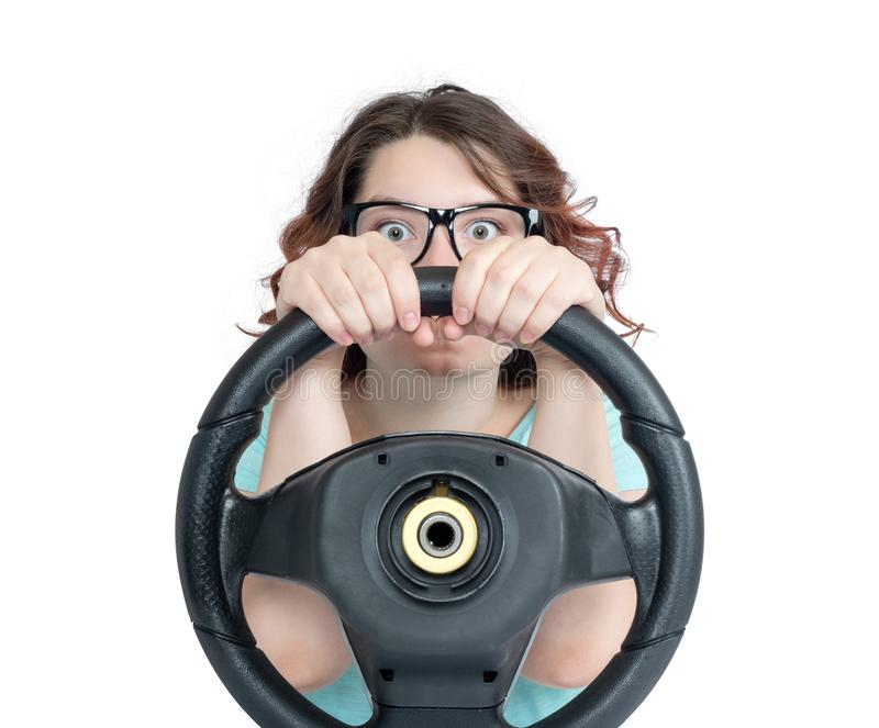 Ragazza divertente in automobile dell'autista di vetro con un volante, isolato su fondo bianco immagini stock