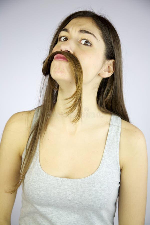 Ragazza divertente che fa baffi con i suoi capelli lunghi fotografie stock