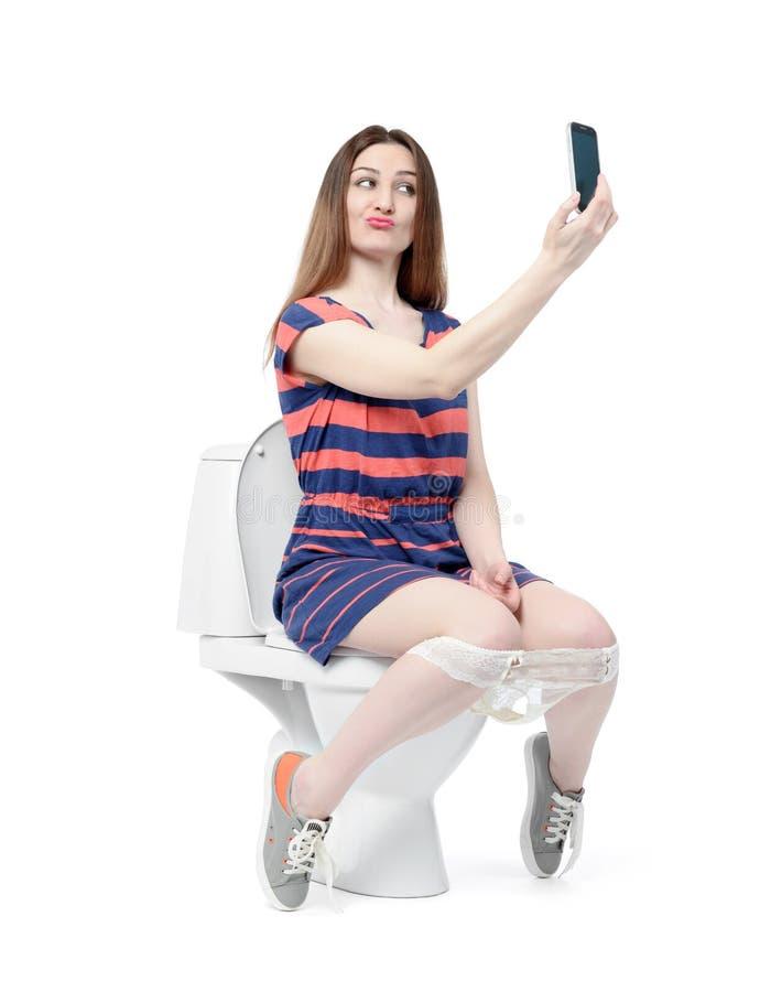Ragazza divertente che fa selfie che si siede sulla toilette fotografia stock