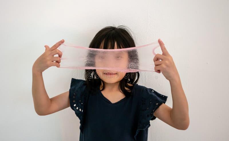 Ragazza divertente che tiene una melma rosa davanti al suo fronte e che guarda attraverso  immagine stock libera da diritti