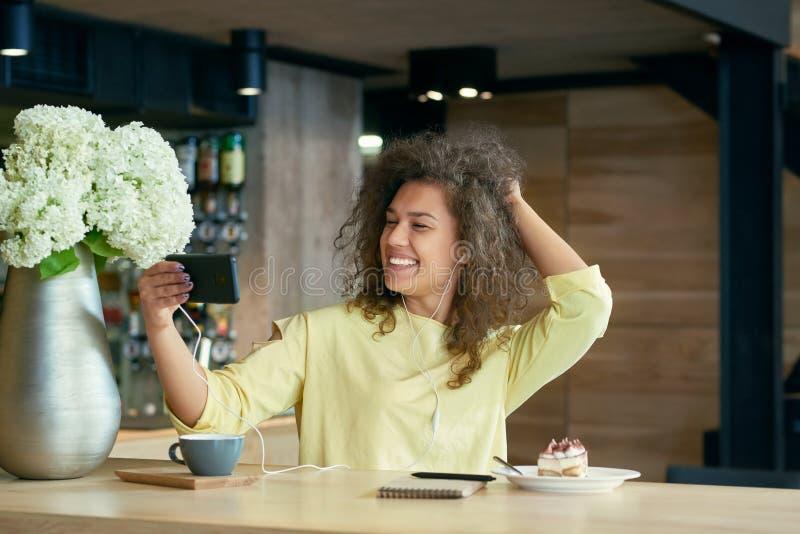 Ragazza divertente con capelli ricci che prendono selfie che si siede sulla tavola di legno del ` s del ristorante fotografia stock