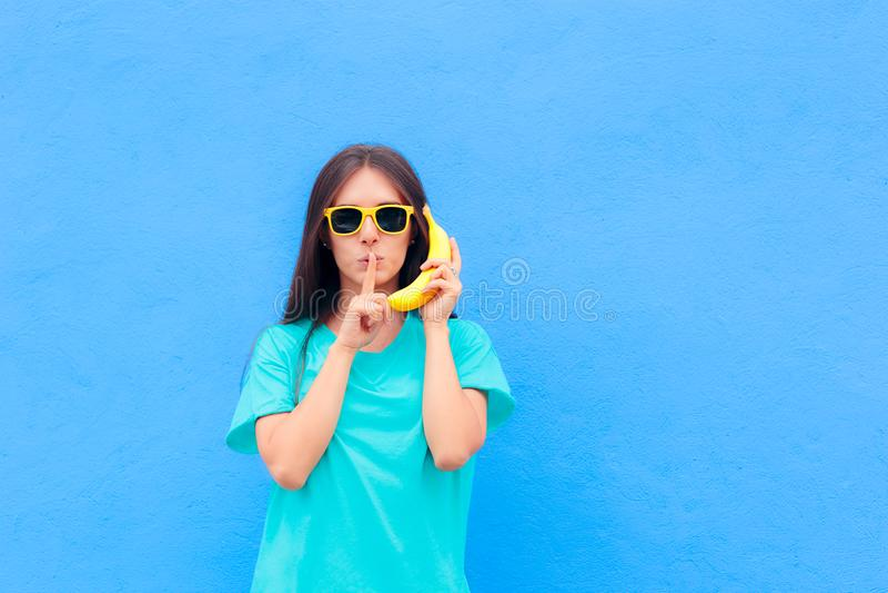 Ragazza divertente con gli occhiali da sole ed il telefono della banana su fondo blu fotografia stock libera da diritti