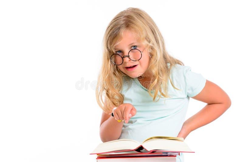 Ragazza divertente con il mucchio dei libri e dei vetri rotondi fotografia stock libera da diritti