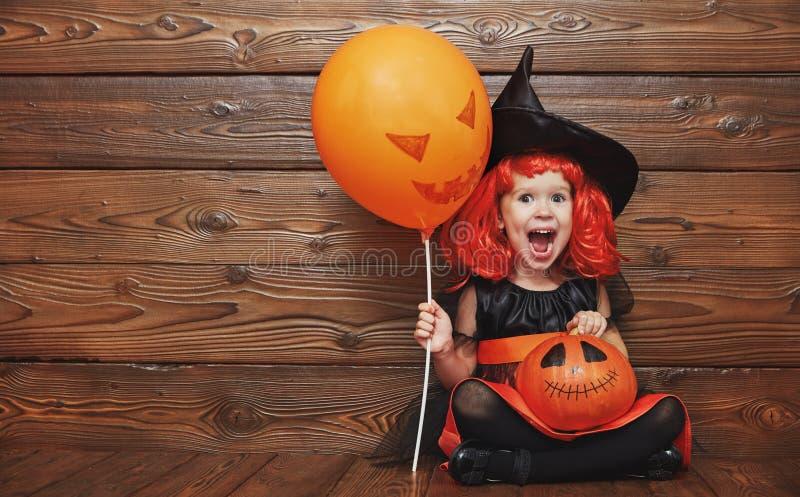 Ragazza divertente del bambino in costume della strega per Halloween con la zucca Ja fotografie stock