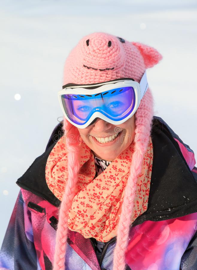 Ragazza divertente dello snowboard con il cappello del maiale immagini stock