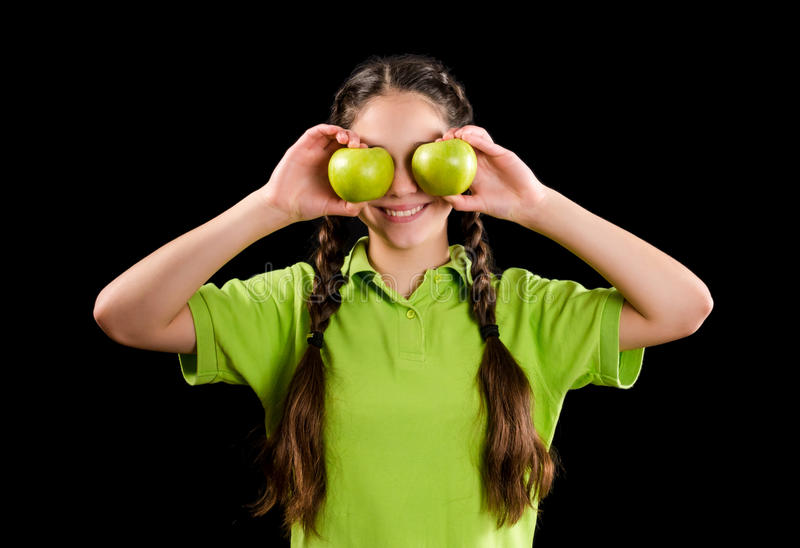 Ragazza divertente emozionante con la mela verde sugli occhi fotografia stock