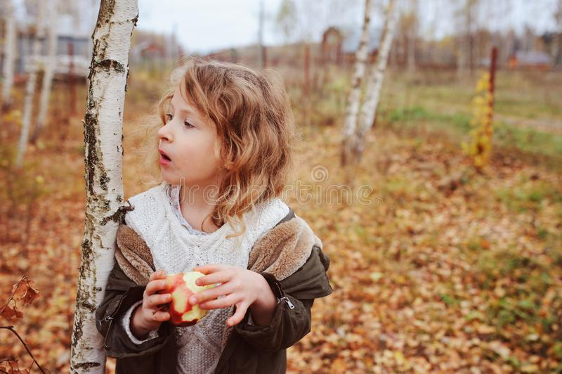 ragazza divertente felice del bambino che mangia mela fresca nella foresta di autunno fotografia stock libera da diritti