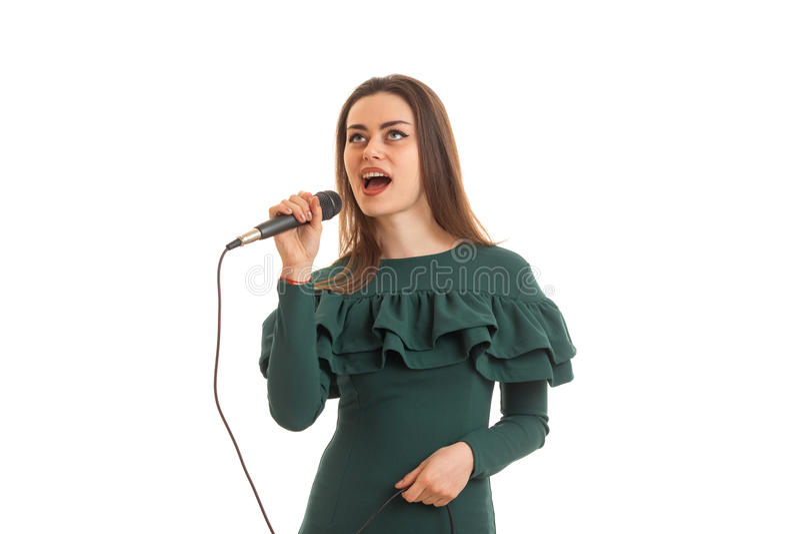 Ragazza divertente in vestito verde che canta un karaoke immagini stock