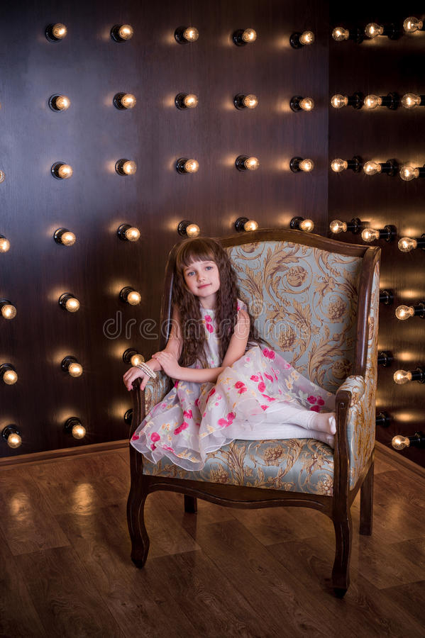 Ragazza dolce che si siede in una sedia costosa fotografia stock
