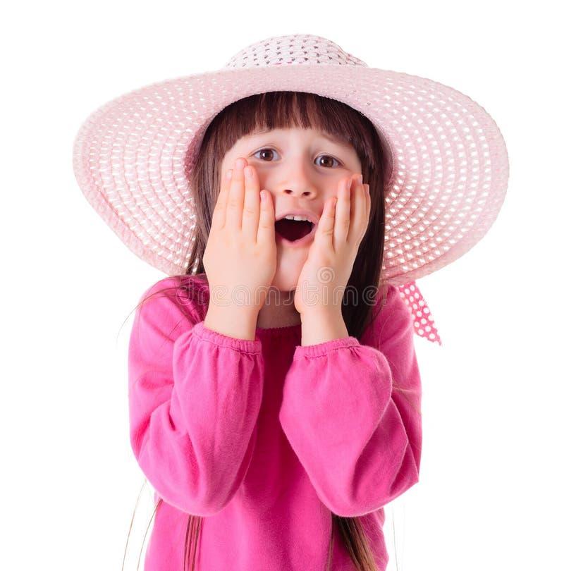 Ragazza domandantesi che porta il cappello rosa del sole fotografia stock libera da diritti
