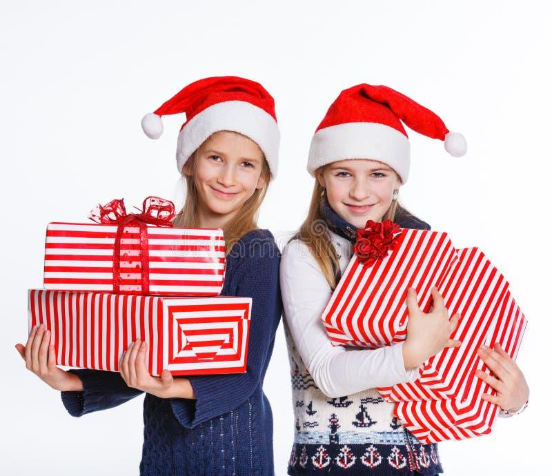 Ragazza due in cappello di Santa con il contenitore di regalo fotografia stock