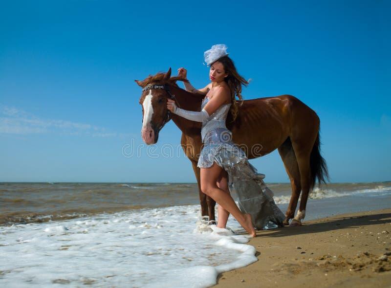Ragazza e cavallo alla spiaggia fotografia stock