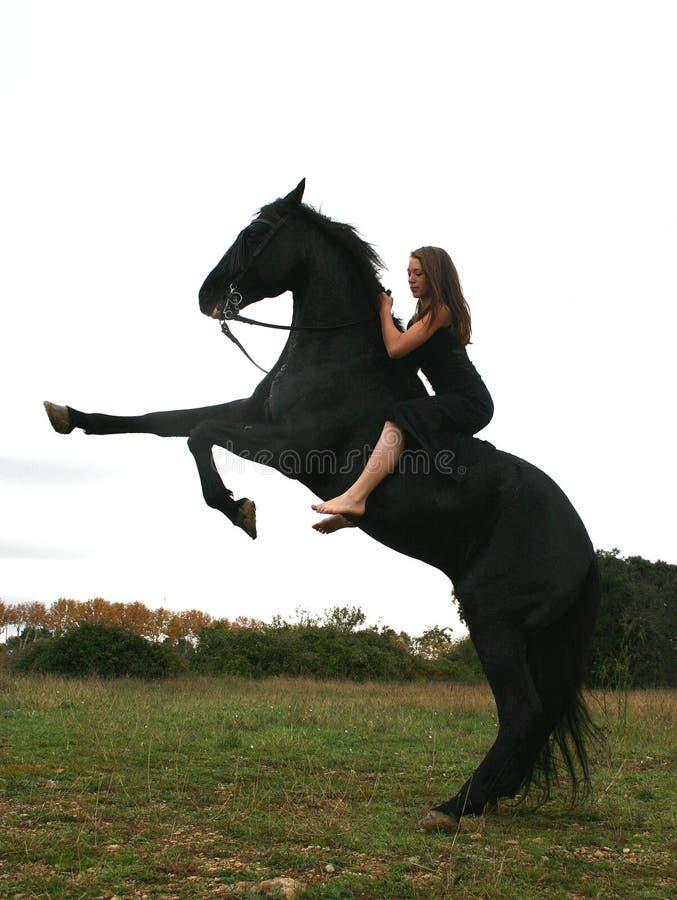 Ragazza e cavallo nero immagine stock