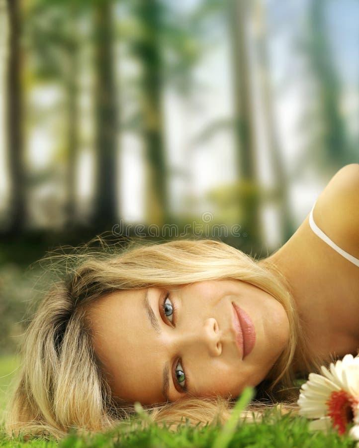 Ragazza e fiore graziosi in erba immagini stock libere da diritti