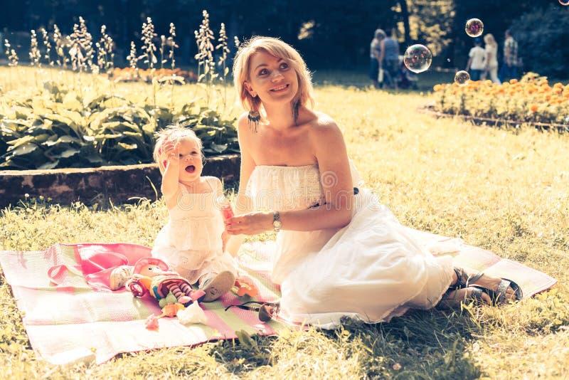 Ragazza e mamma che soffiano le bolle di sapone immagini stock libere da diritti