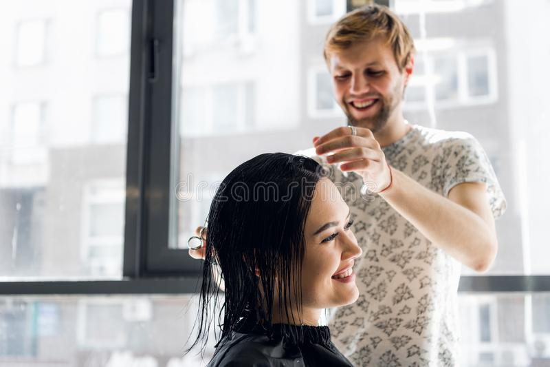 Ragazza e parrucchiere di risata che parlano e che sorridono mentre facendo un nuovo taglio di capelli o acconciatura immagine stock