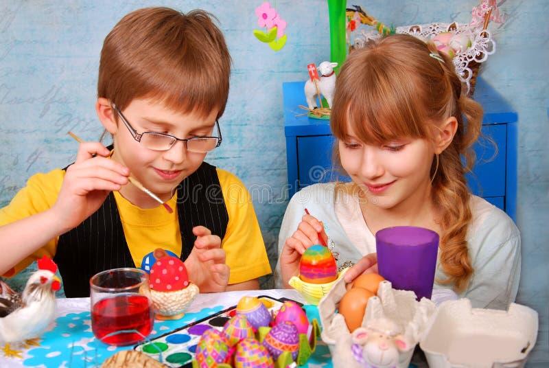 Ragazza e ragazzo che dipingono le uova di Pasqua fotografie stock libere da diritti