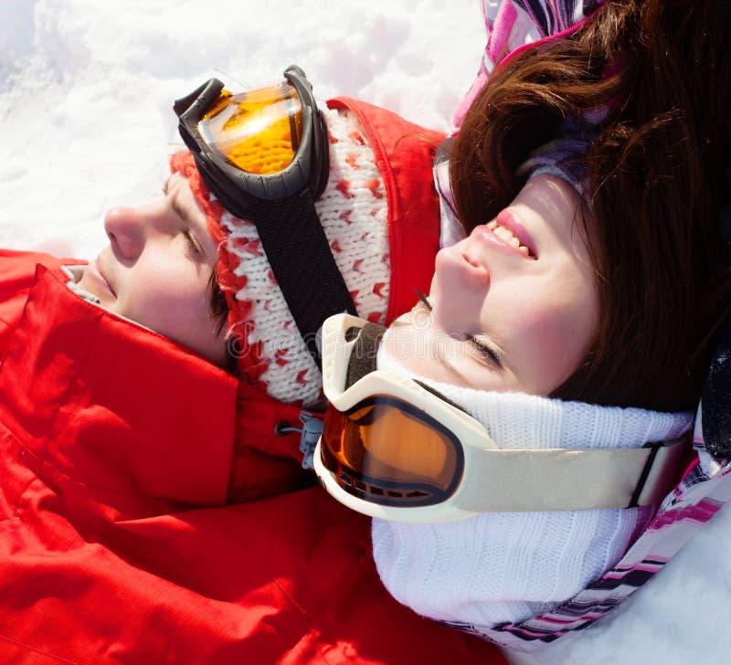 Ragazza e ragazzo che si trovano sulla neve fotografia stock