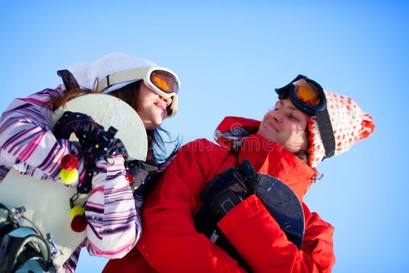 Ragazza e ragazzo con gli snowboards fotografia stock libera da diritti