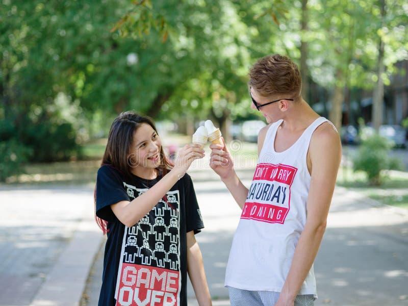 Ragazza e ragazzo di datazione che mangiano il gelato su un fondo del parco Rilassamento romantico e sveglio delle coppie Concett fotografia stock