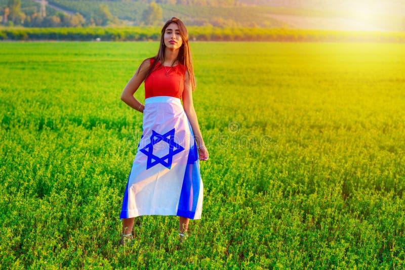 Ragazza ebrea con la bandiera di Israele su paesaggio di stupore di bella estate fotografie stock