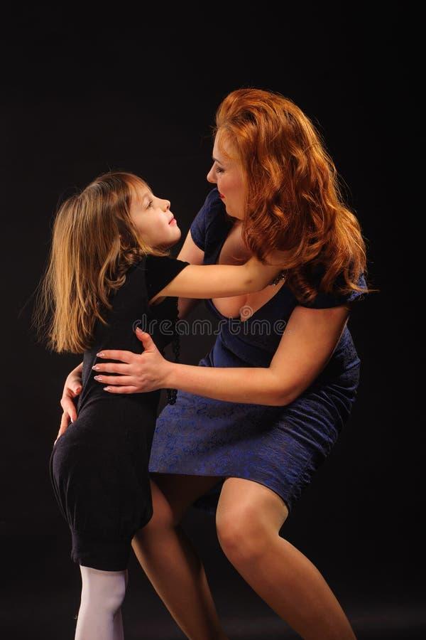 Ragazza ed abbraccio maturo della madre fotografie stock